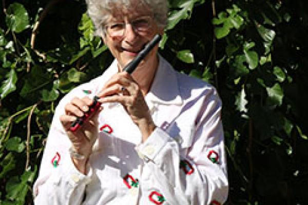 Professor Katherine Borst Jones poses with her red composite piccolo