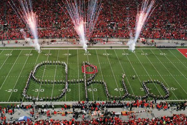 The Ohio State Marching Band forms a Script Ohio with fireworks in the background