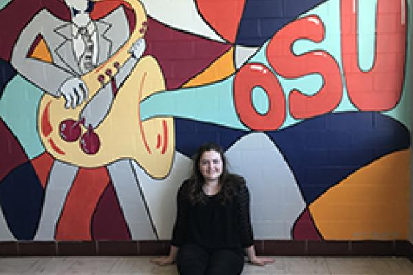 Audrey Watkins poses with her mural in Hughes Hall